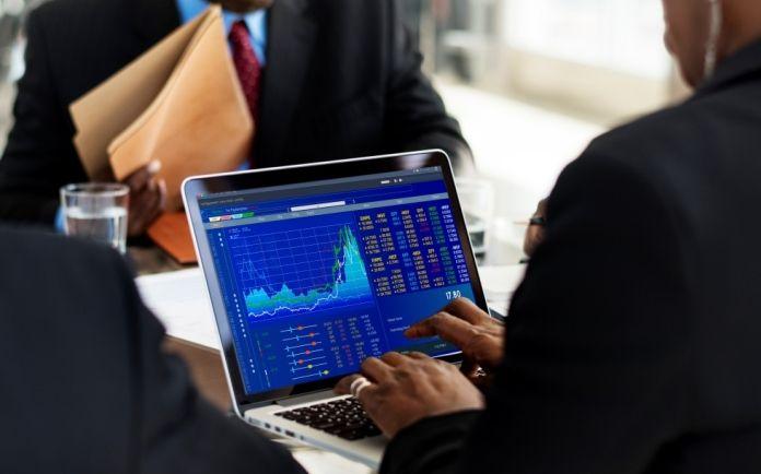 Ejecutivos analizando mercados en ordenador
